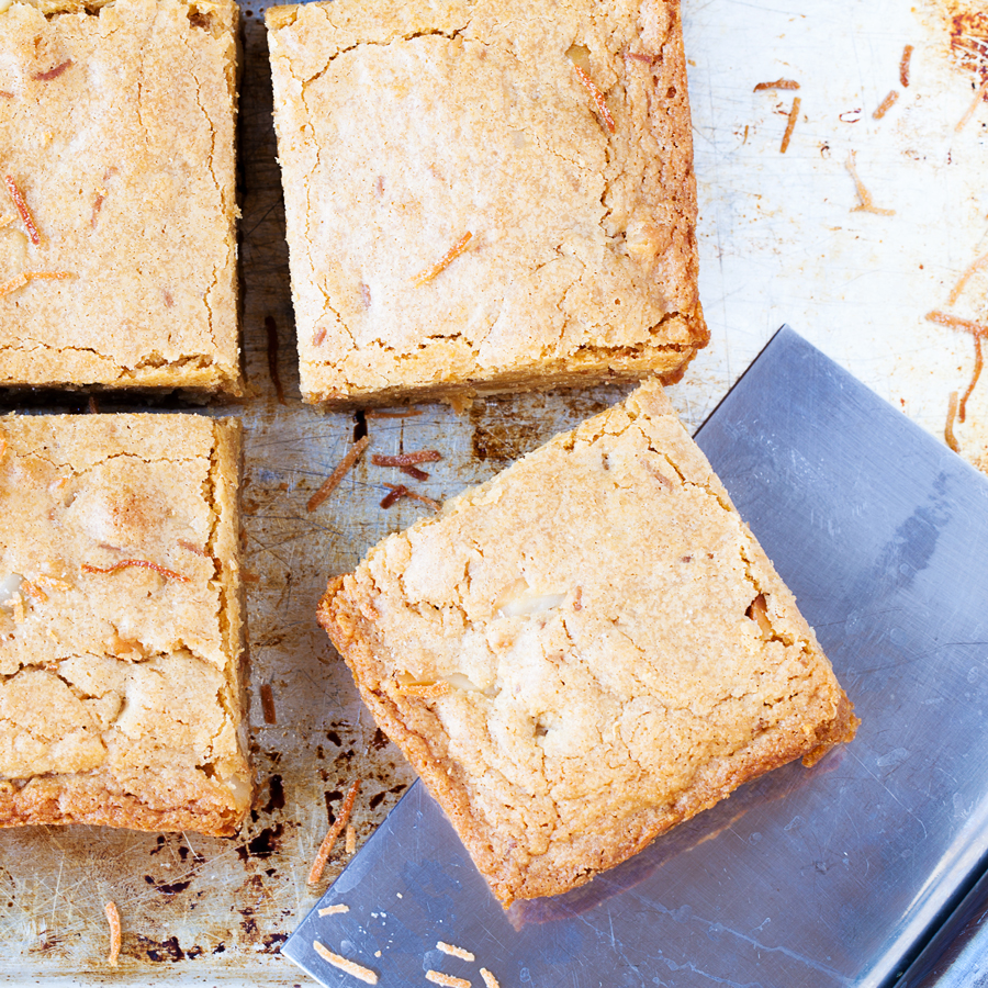 The PKP Way | A cookie-like exterior and a cake-like interior, make these Coconut Macadamia Nut Blondies the perfect transportable treat for any celebration.