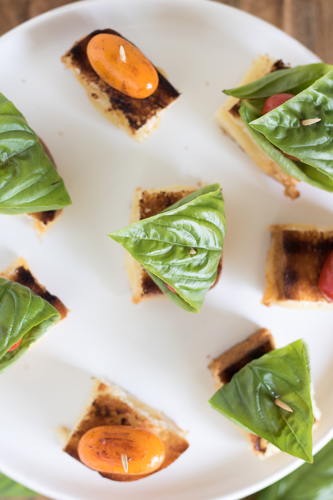 Grilled Cheese Tomato Bites topped with blistered sweet grape tomatoes and fresh basil leaves are an afternoon snack recipe you can't resist.