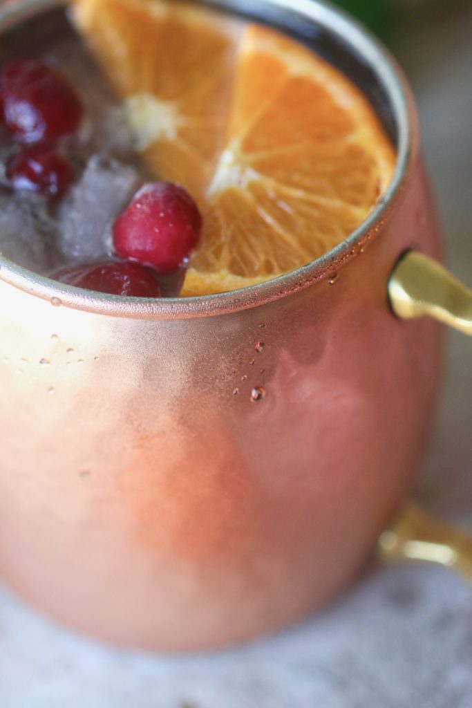 Looking for a refreshing holiday drink? Grab a copper mug and make these amazing Cranberry Orange Moscow Mules! Zesty, fresh and delicious; this cocktail is exactly what your party needs.